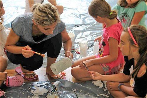 inštruktorka ukazuje deťom ako maľovať pohár na tábore