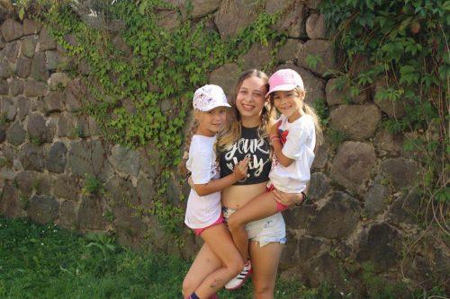 dievča drží na rukách dve menšie dievčatká v letnom tábore