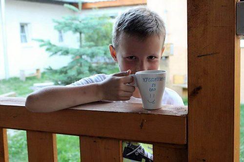 chlapček s hrnčekom na terase v tábore