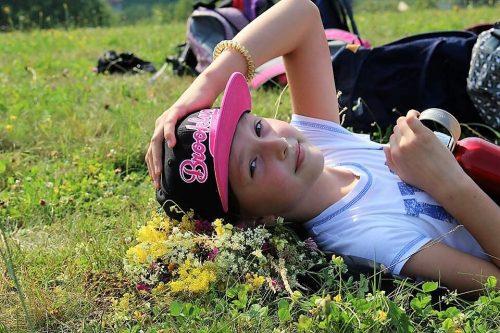 chlapec oddychujúci na tráve v detskom letnom tábore Fantázia
