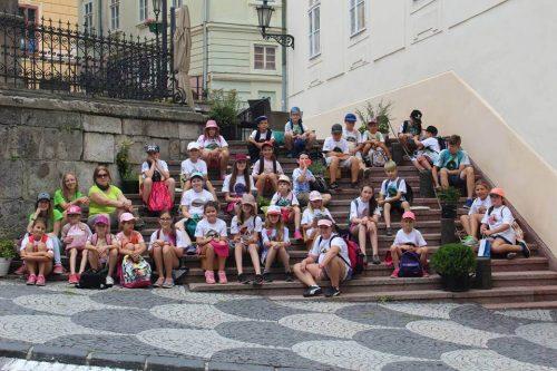 deti sediace na schodoch na táborovom výlete