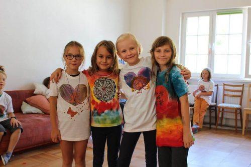 deti s farebnými tričkami na tábore