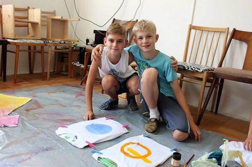 chlapci maľujú tričká v detskom tábore