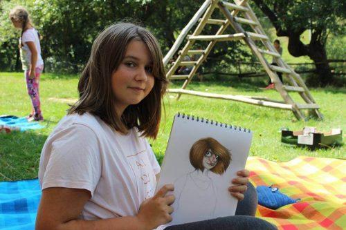 dievča ukazuje svoju kresbu na tábore