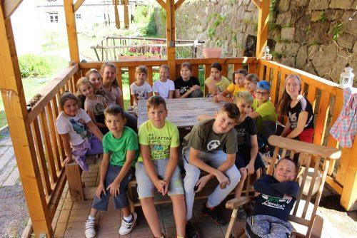 deti sediace okolo stola na terase v detskom tábore
