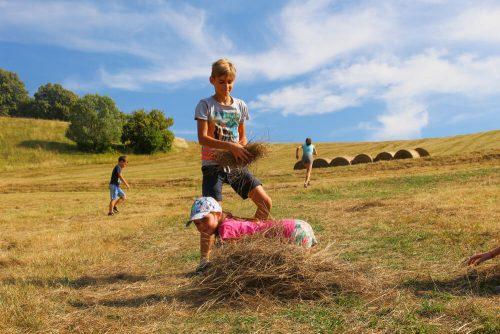 chlapec a dievča sa hrajú so senom na tábore