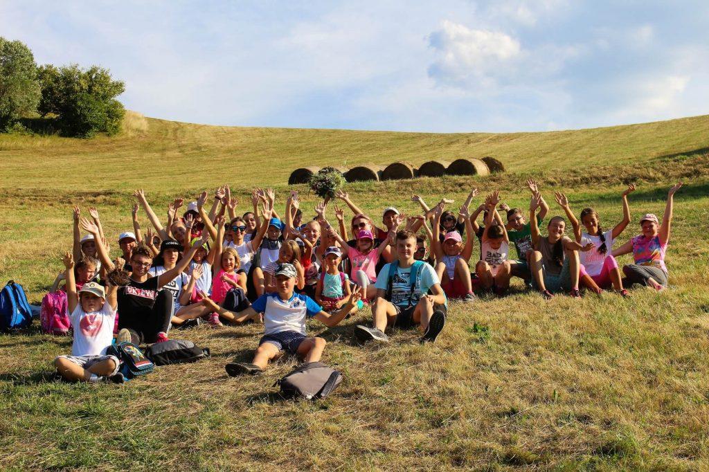 deti v detskom tábore na lúke so zdvihnutými rukami