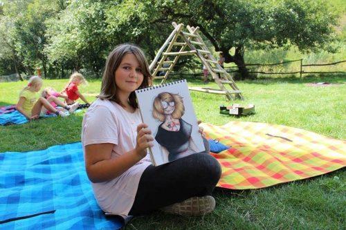 dievča ukazujúce svoju maľbu vonku na deke