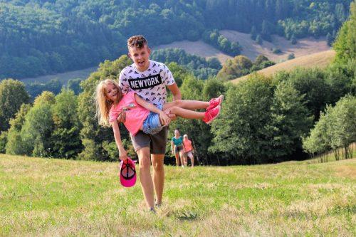 chlapec nesie dievča na lúke v detskom tábore